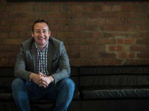 Pete Watson sitting alone on a large sofa, smiling