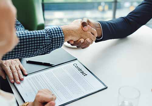 People shaking hands over a contract