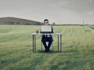 A man sitting at a desk with a laptop in the middle of a field