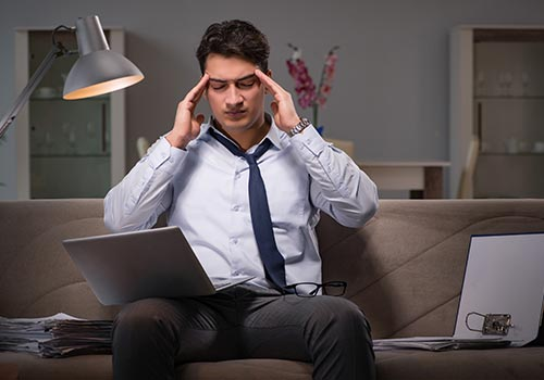 Stressed man working on a laptop in his living room
