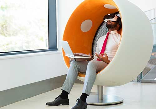 Relaxed IT guy chilling in a pod with his laptop on his lap