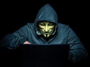 Hacker with a mask on sitting at a laptop in a dark room