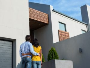 A couple standing in front of their new modern home