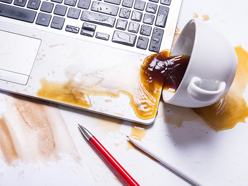 a cup of coffee that has been spilled onto a laptop